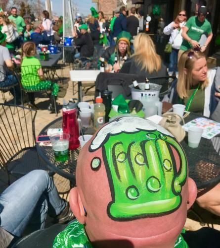 St. Paddy's Day Tinley Park Parade face painting green beer on a bald head.